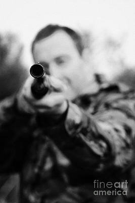 Man In Camouflage Clothes Takes Aim At Camera With Shotgun On December Shooting Day Print by Joe Fox