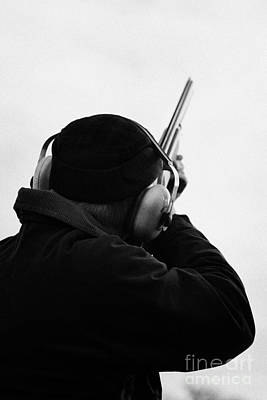 Man In Cap And Ear Defenders Takes Aim Into Sky With Shotgun On December Shooting Day Print by Joe Fox