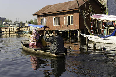 Tourist Photograph - Man Rowing A Family In A Wooden Boat In Front Of Non-tourist Area In Dal Lake by Ashish Agarwal