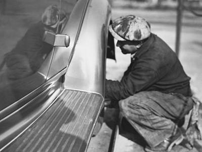 Crouched Photograph - Mechanic Working On Car by Underwood Archives