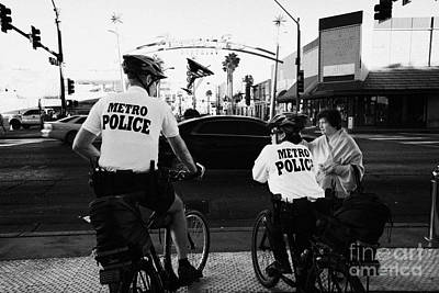 metro police bicycle cops help a tourist with directions in downtown Las Vegas Nevada USA Print by Joe Fox