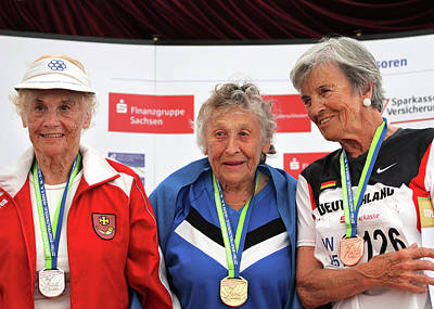 Older Female Athletes On Medals Rostrum Print by Alex Rotas