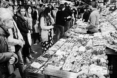 people buying chocolates on display inside the la boqueria market in Barcelona Catalonia Spain Print by Joe Fox