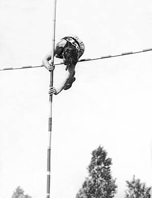 Vaults Photograph - Pole Vaulter Over The Bar by Underwood Archives