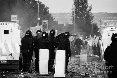 Police Officers In Riot Gear Face Rioters On Crumlin Road At Ardoyne Print by Joe Fox