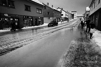 pools of thawing water from ice on main shopping street storgata Honningsvag finnmark norway europe Print by Joe Fox