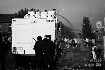 Psni Riot Officers Behind Water Canon During Rioting On Crumlin Road At Ardoyne Print by Joe Fox