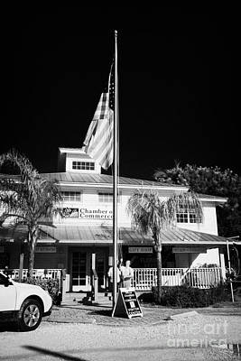 Raising The American Flag On A Flagpole Outside The Chamber Of Commerce Building In Key Largo Florid Print by Joe Fox