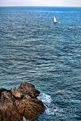 Sailboat Along Rocky Coastline Print by Olivier Le Queinec