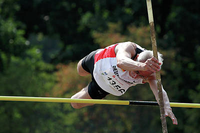 Vaults Photograph - Senior Pole Vaulter Clearing The Bar by Alex Rotas
