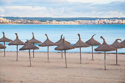 Straw Umbrellas On Empty Beach Print by Christina Rahm