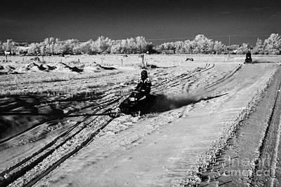 two men on snowmobiles crossing frozen fields in rural Forget Saskatchewan Canada Print by Joe Fox
