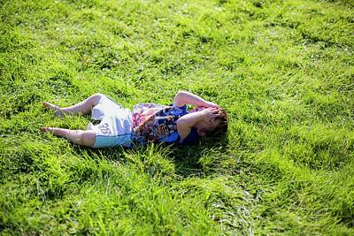 Obscured Face Photograph - Young Boy Lying On Grass by Samuel Ashfield