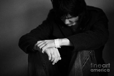Young Dark Haired Teenage Man Sitting On The Floor With Back Against The Wall In The Fetal Position  Print by Joe Fox