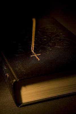 Gold Cross Pendant Resting On A Book Print by Philippe Widling