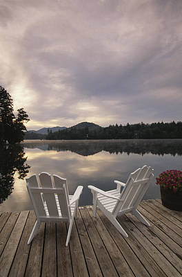 Etc. Photograph - A Pair Of Adirondack Chairs On A Dock by Michael Melford