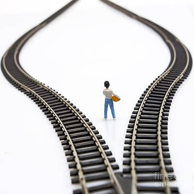 Considering Photograph - Figurine Between Two Tracks Leading Into Different Directions Symbolic Image For Making Decisions. by Bernard Jaubert