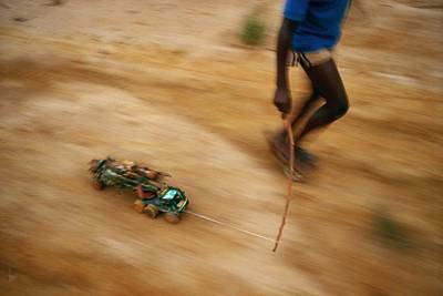 Etc. Photograph - A Child Pulling His Toy Truck At High by Michael Nichols