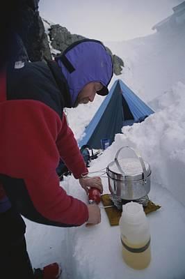 A Climber Cooks At A Snowy Camp High Print by Gordon Wiltsie