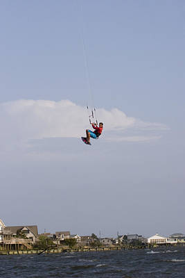 Kite Boarding Photograph - A Kiteboarder Jumps High Over Beach by Skip Brown
