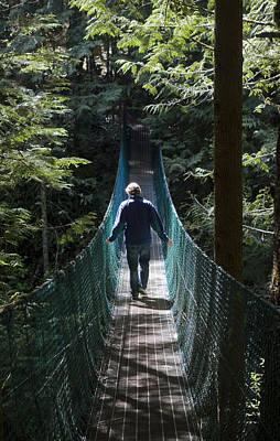 A Man Walks Across A Suspension Bridge Print by Taylor S. Kennedy
