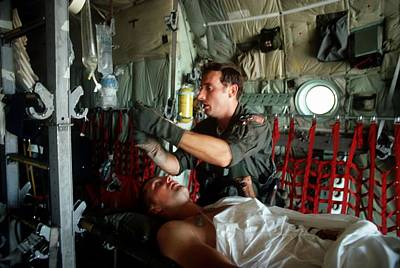 A Medic Adjusts The Intravenous Drip Print by Everett