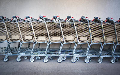 A Row Of Grocery Carts Stacked Together Print by Marlene Ford