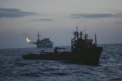 Cranes And Derricks Etc Photograph - A Trawler Passes Near An Oil Rig by Bill Curtsinger