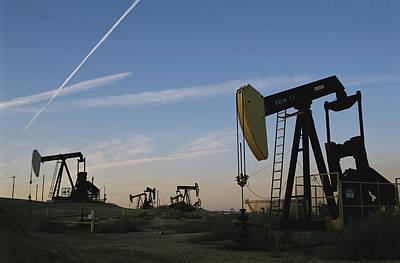 Cranes And Derricks Etc Photograph - A Twilight View Of Oil Derricks by Sarah Leen