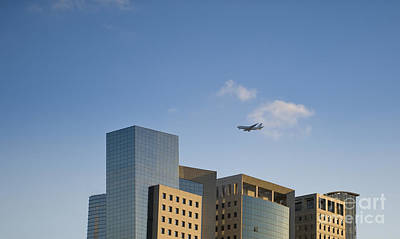 Airplane Flying Over Office Buildings Print by Noam Armonn