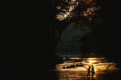 Backlit View Of Couple Flyfishing Print by Skip Brown
