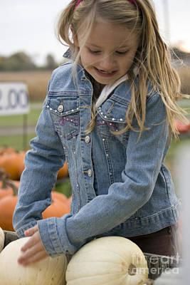 Cute Little Girl Picking A Pumpkin Print by Christopher Purcell