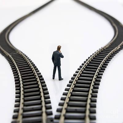 Figurine Between Two Tracks Leading Into Different Directions  Symbolic Image For Making Decisions Print by Bernard Jaubert