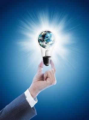 Hand Holding Light Bulb With Globe  Print by Setsiri Silapasuwanchai