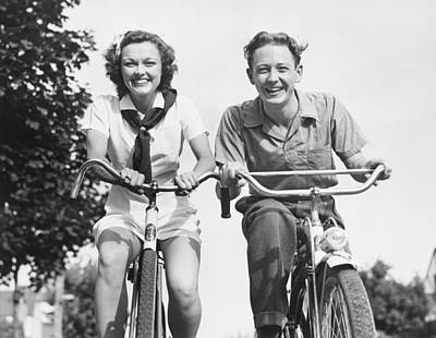 Man And Woman Riding Bikes, (b&w), Low Angle View Print by George Marks