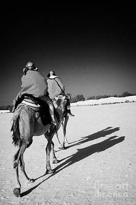Camel Photograph - two tourists on camels return to base in the sahara desert at Douz Tunisia by Joe Fox