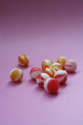 Unwrapped Hard Candies On Pink Paper Print by Asia Images