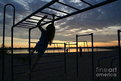 Water Photograph - Young Girl Swinging On Monkey Bars At Dusk by Christopher Purcell