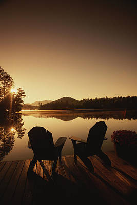 Natural Forces Photograph - A Pair Of Adirondack Chairs On A Dock by Michael Melford