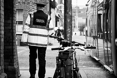 irish garda police sergeant on foot patrol in dublin city centre Ireland Print by Joe Fox