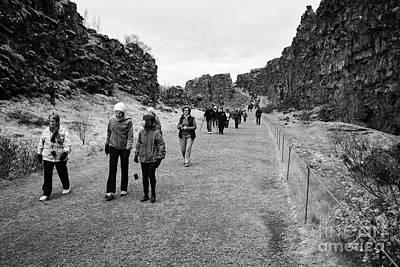 tourists walk through the Almannagja fault line in the mid-atlantic ridge north american plate Print by Joe Fox
