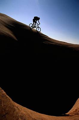 A Cyclist Riding On The Slick Rock Print by Bill Hatcher