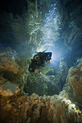 Bahama Islands Photograph - A Diver Ascends A Deep Shaft In Dans by Wes C. Skiles