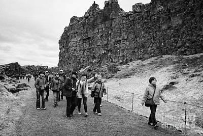 asian tourists walk through the Almannagja fault line in the mid-atlantic ridge north american plate Print by Joe Fox