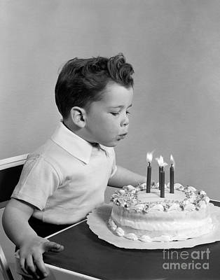 Party Birthday Party Photograph - Boy Blowing Out Candles On Cake, C.1950s by H. Armstrong Roberts/ClassicStock