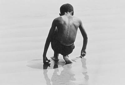 Crouched Photograph - Boy Playing In The Sand At Coney Island by Nat Herz