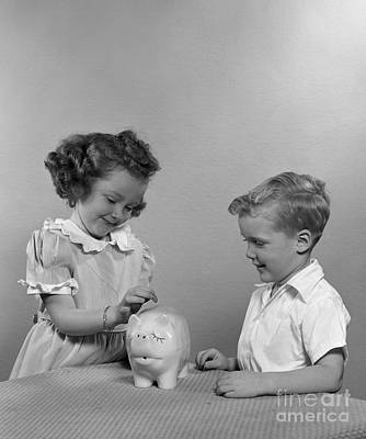 Girl Putting Coin Into Piggy Bank Print by H. Armstrong Roberts/ClassicStock