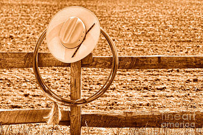 Hat And Lasso On A Fence - Sepia Print by Olivier Le Queinec