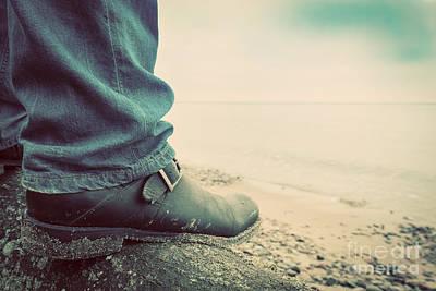 Man In Jeans And Elegant Shoes Standing On Fallen Tree On Wild Beach Looking At Sea Print by Michal Bednarek