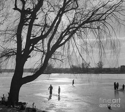 Wintry Landscape Photograph - People Ice Skating On A Frozen Over Lake by German School